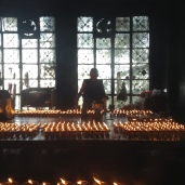 A monk lighting prayer candle at Tsuglagkhang